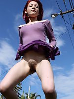 Redheaded Sofia, with her pale skin, and thick curly pubes plays around naked by the roadside. We see up her skirt, down her top, and all the way inbetween her arse cheeks